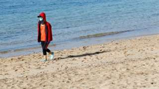 A woman wearing a face mask walks on a beach in Lanzarote