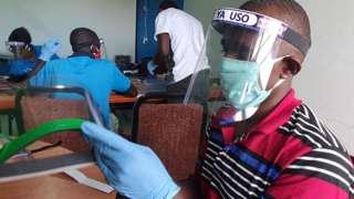 Workers in Dar es Salaam prepare face shields