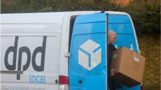 A DPD delivery worker next to his van