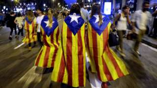 """People wearing """"Estelada"""" Catalan flags on their backs leave after taking part in a protest in Barcelona (3 October 2017)"""