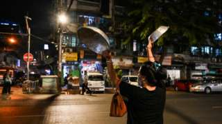 A woman clatters pans to make noise after calls for protest went out on social media in Yangon