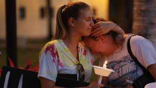 Two girls cry and comfort each other at Parkland vigil