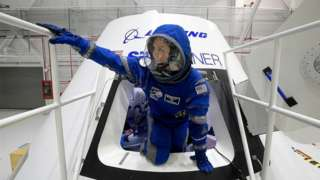 Boeing propulsion engineer Monica Hopkins climbs out of a mockup of the CST-100 Starliner crew module, while wearing a newly-designed spacesuit, during an exclusive look at some of the things that Boeing is doing