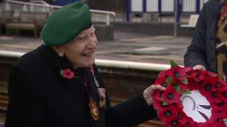 Harry Billinge smiles while holding wreath
