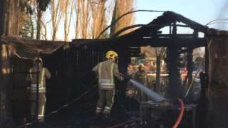 Fire fighters hose down burnt enclosure