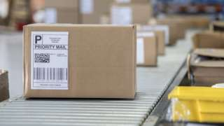 A parcel sitting on a conveyor belt in a sorting office