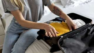 Stock image of a woman with a suitcase in a hotel room