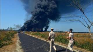 Policemen gesture as they ask people to move to a safer place as smoke rises following an explosion at an oil well
