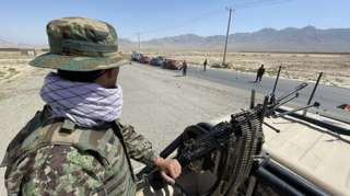 An Afghan soldier stands guard at a checkpoint