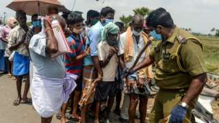 A policeman (R) holding a stick regulates the crowd as people line up to buy alcohol at a liquor shop after the government eased a nationwide lockdown imposed as a preventive measure against the COVID-19 coronavirus, on the outskirts of Chennai on May 7, 2020.
