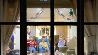Residents of a care home in Liverpool seen through a window