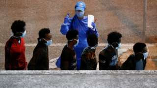 Rescued migrants are being checked by a United Nations High Commissioner for Refugees (UNHCR) worker