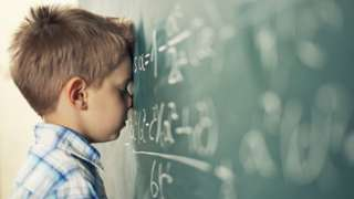 Young boy leans against chalkboard