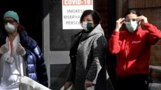 Women wearing protective face masks stand outside the new wards set up at Cardarelli hospital