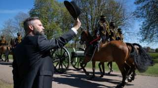A person salutes the King's Troop Royal Horse Artillery as they make their way down the Long Walk towards Windsor Castle