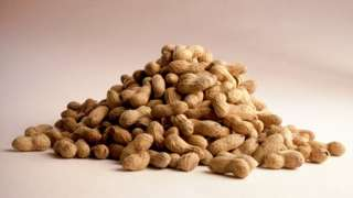 A photo of a mound of peanuts still in their shells
