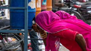 A Rajasthani woman drinks water