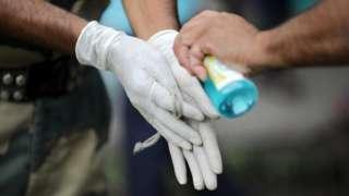 Des personnes utilisent un désinfectant pour les mains à Kolkata, en Inde, en juillet