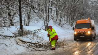 An employee of the Departmental Infrastructure Authority clears fallen tree branches from a road leading to the French Alps ski resorts of Les Menuires and Val Thorens on January 4, 2018