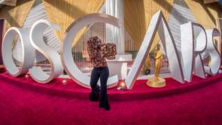 A TV reporter poses beside an Oscars statue on the red carpet area on the eve of the 92nd Oscars ceremony in 2020
