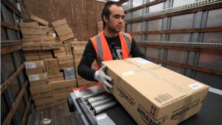 An Amazon worker loads a package on a truck