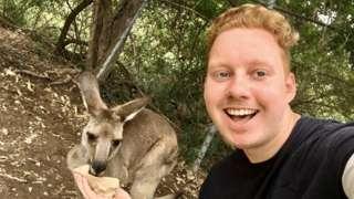 Luke Shortland with a kangaroo on his year abroad in Australia