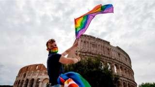 A man waves a Rainbow Flag past the Coliseum monument on 13 June, 2020