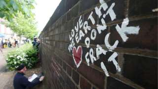 Anti-fracking protester (demonstrator) writes messages on a wall with chalk during a demonstration in England