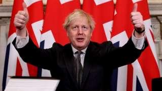 Boris Johnson celebrates signing the trade deal