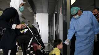 A health worker takes the temperature of a child at Damascus airport on 1 October 2020