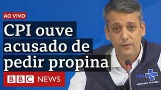 Foto de Roberto Dias usando camisa branca e colete do Ministério da Saúde, acompanhada do seguinte texto: Ao vivo - CPI ouve acusado de pedir propina