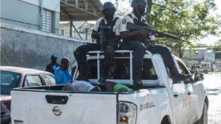 Police in a truck with some recaptured prisoners