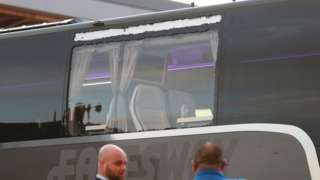 Real Madrid team bus showing damage to a window