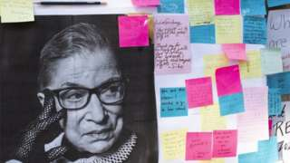 A photo and messages left in remembrance of the late Supreme Court Justice Ruth Bader Ginsburg are placed outside of the Harvard Law School library
