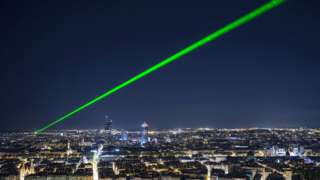 A bright green laser beam shining in the night sky above Lyon, France