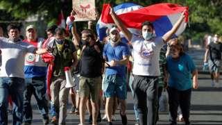 pessoas com máscaras e cartazes protestam na ruas