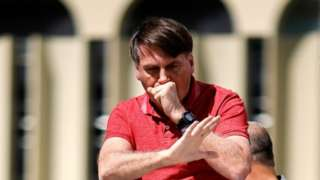 Jair Bolsonaro coughs at a rally in April 2020