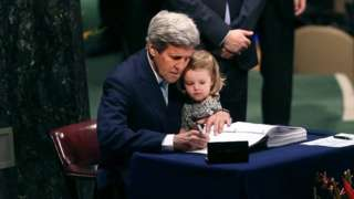 John Kerry is joined by his granddaughter as he signs the Paris climate agreement in 2016