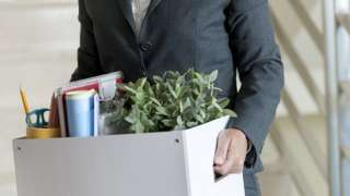 Woman in business suit carrying box out of office, having just been made redundant
