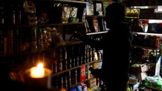 A shop vendor works by candlelight in Buenos Aires, Argentina
