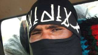 A close-up shot of an Islamist militant wearing a black fabric on his face showing only his eye.