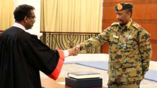 """A picture released by Sudan""""s Presidential Palace shows General Abdel Fattah al-Burhan, the head of Sudan""""s ruling military council, during a swearing in ceremony i"""