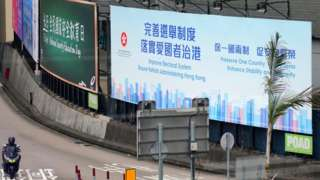 A motorcyclist rides past a billboard reading 'Improve Electoral System, Ensure Administering Hong Kong, Preserve One Country, Two System, Enhance Stability and Prosperity' in the street on March 31, 2021 in Hong Kong, China
