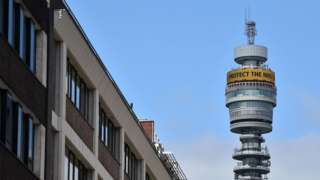 London's BT tower is seen rising above the buildings around it, with satellite dishes and communications equipment dotted around its circumference