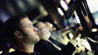 A young man gambling at a fixed odds terminal