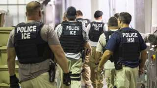 A ICE handout photo showing US immigration officers in a plant in Mississippi