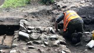 Archeolwgwyr yn dod o hyd i wal gerrig ar y safle
