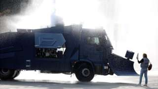 An opposition supporter stands next to a police water cannon truck during a rally to reject the presidential election results in Minsk on 4 October 2020