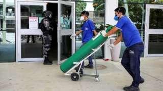 Dois homens de máscara carregam carrinho com tanque de oxigênio, em frente a porta de hospital
