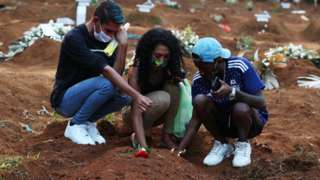Relatives mourn at cemetery in Brazil